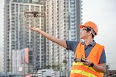 Young Asian engineer flying drone over construction site. Using unmanned aerial vehicle (UAV) for land and building site survey in civil engineering project. poster