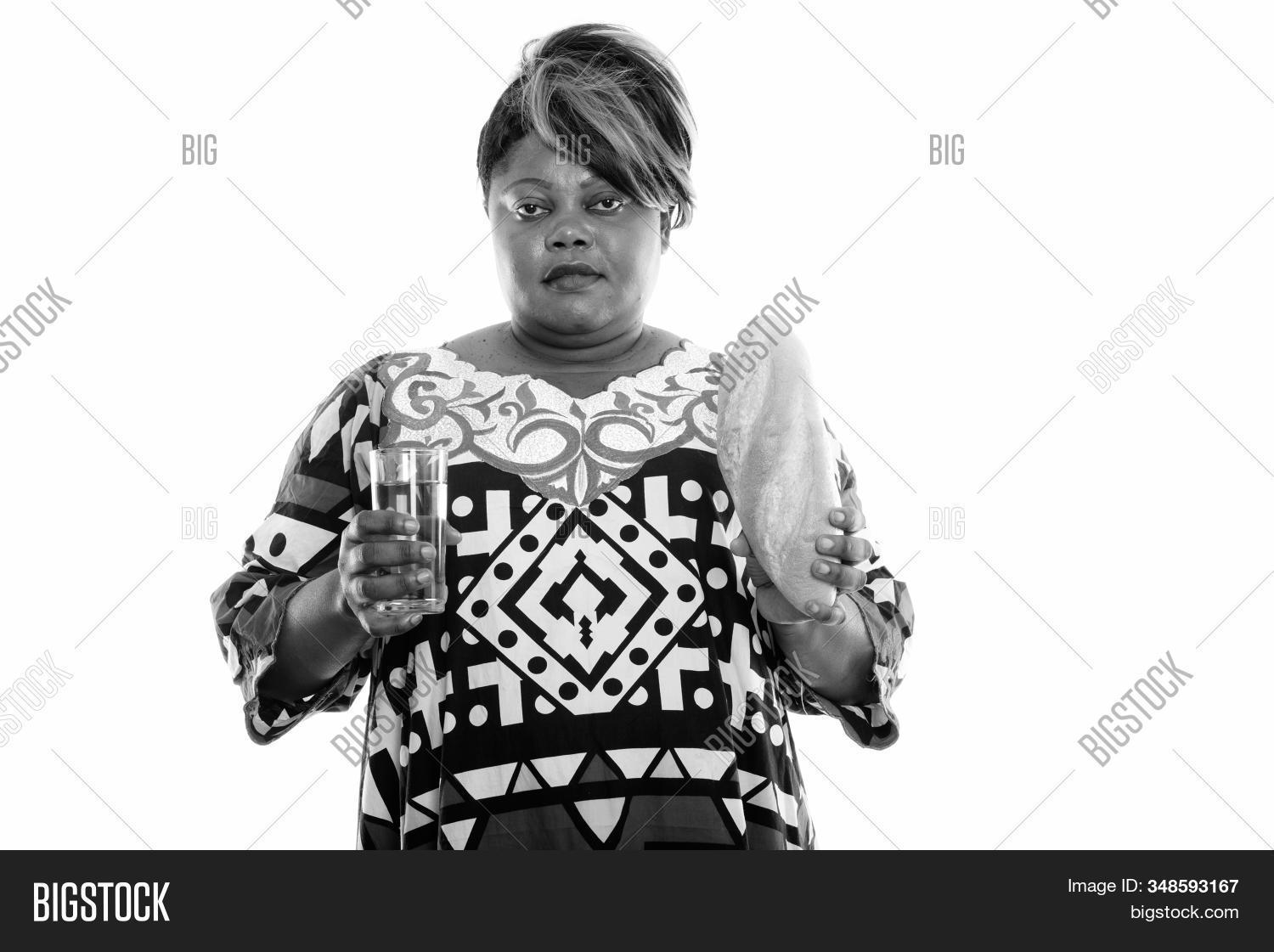 Studio Shot Of Fat Black African Woman Holding Glass Of Beer And Bread