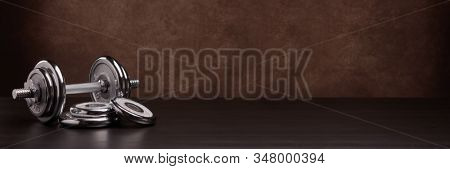 Steel dumbbell and weights on dark wooden surface on brown background with copy space. Sports bodybuilding equipment. Fitness, sport, healthy lifestyle concept. Extra wide panorama banner background