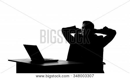Silhouette Of Male Smugly Sitting On Chair After Successful Completion Of Deal
