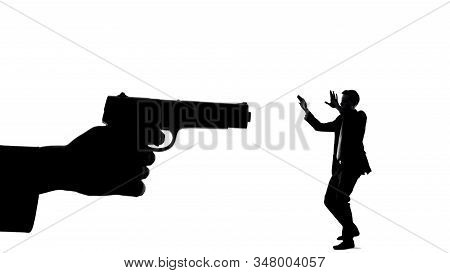 Silhouette Of Hand With Gun Threatening Minuscule Man, Life In Danger Death Risk