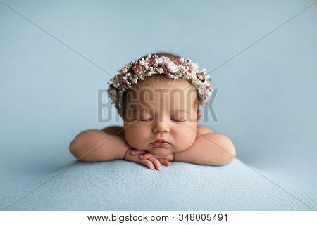 Newborn In Floral Headband On The Blue Blankets Folded Handles.