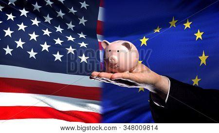 Us Investment In Eu, Businessman Hand Holding Piggybank On Flag Background