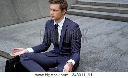 Handsome Office Worker Calming Down After Stressful Working Day, Lotus Position