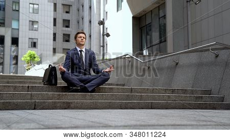 Handsome Businessman Sitting In Lotus Position, Calming Down Stressful Situation