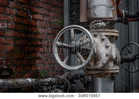 Old Water Valve.old Water Valve On A Background Of A Brick Wall.large And Rusty Valve On The Water P