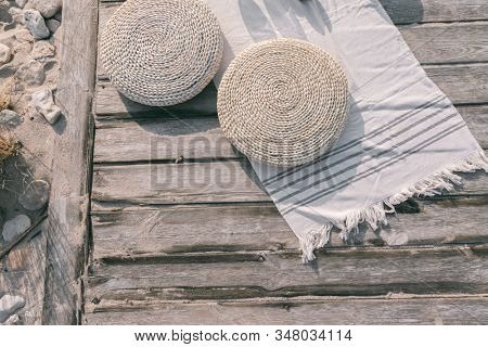 Boho eco styled beach essentials on sand by sea. Wicker cushions and beach towel on wooden backround, top view.