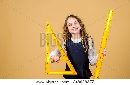 School Student Learning Geometry. Pupil Girl With Big Rulers. Small Girl Back To School. Stem School