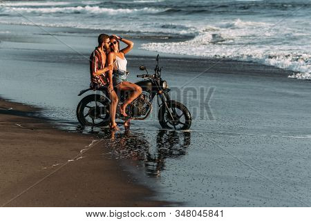 A Couple In Love On The Beach Meets The Sunset. Beautiful Couple On A Motorbike Meets Sunset By The