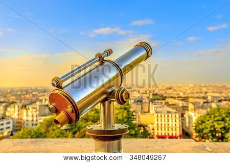 Closeup Of Look-out Binoculars With View Above Urban Cityscape Skyline Of Paris At Sunset Light From