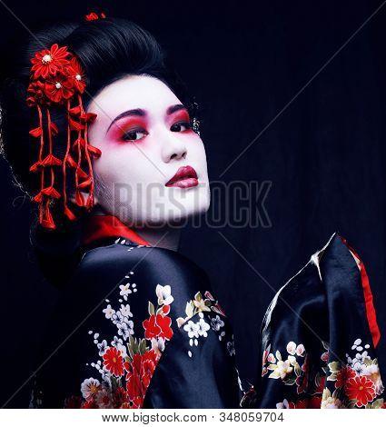 Young Pretty Geisha In Kimono With Sakura And Decoration On Black Background