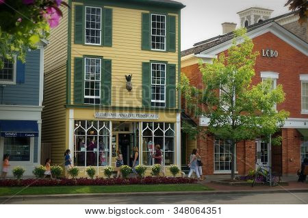 Niagara-on-the-lake, Canada - 06 19 2016: Tourists On The Picturesque Queen Street Of A Canadian Tou