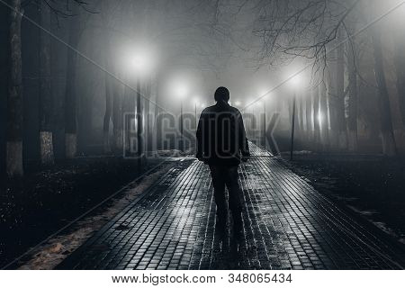 Sad Man Alone Walking Along The Alley In Night Foggy Park. Back View