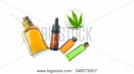Glass Bottles With Cbd Oil, Cbd Balm And Thc Tincture And Hemp Leaves On White Background. Flat Lay