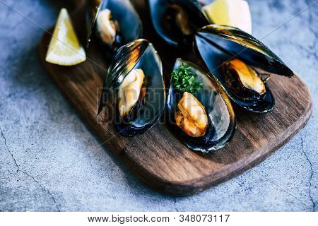 Cooked Mussels With Herbs Lemon And Dark Plate Background / Fresh Seafood Shellfish On Wooden Cuttin