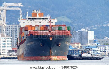 Oakland, Ca - Jan 19, 2020: Tugboats Are Small But Powerful For Their Size. Tugboat Assisting Cargo