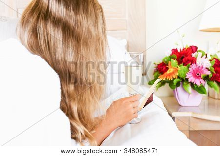 Girl Relaxing In Her Hotel Room With A Glass Of Sparkling Drink And A Book. Vacation, Relaxation, Se