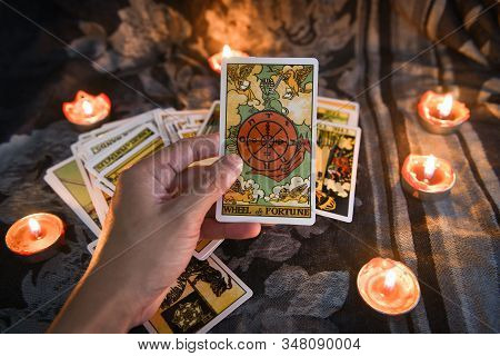 Hand Holding Tarot Card With Candlelight On The Darkness Background For Astrology Occult Magic Illus