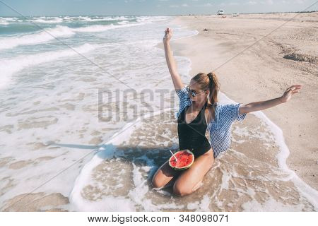 Slim girl in fashion style swimwear eating watermelon at sand beach and enjoying tropical paradise by sea. Perfect summer vacation, good vibes, vegan diet.