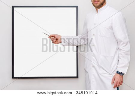 Man In White Uniform Pointing On A Picture Frame Or Poster For Mock Up. Doctor Or Chef Showing Empty