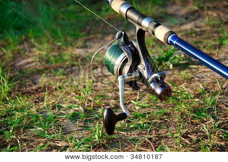 Blue Fishing Reel On The Green Grass