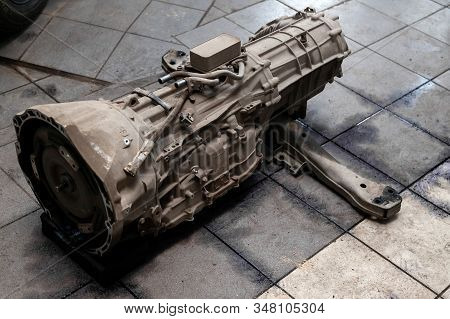 The Used Gearbox Removed From The Car On The Floor Among Other Parts In The Vehicle Repair Workshop.