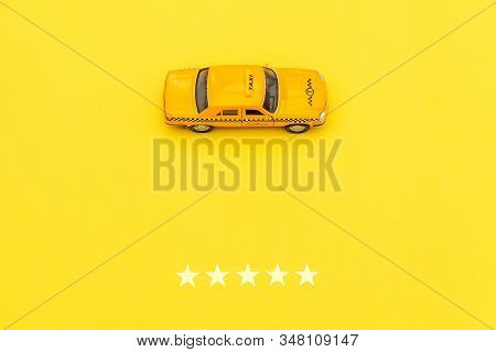 Yellow Toy Car Taxi Cab And 5 Stars Rating Isolated On Yellow Background. Smartphone Application Of