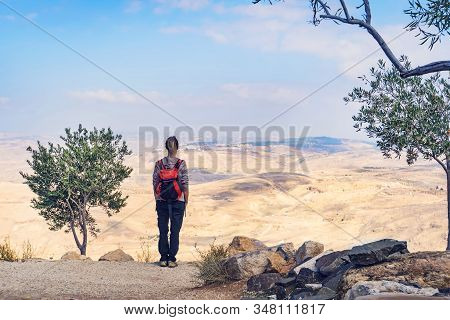 A Backpacker Woman Stands On A Mountain And Looks Out Over The Jordan Desert Near The Dead Sea. The