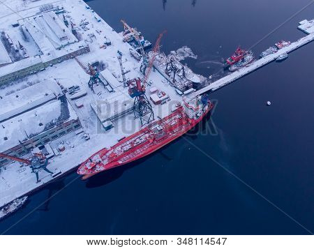 Commercial North Arctic Port Is Loading Containers Onto Cargo Tanker Ship. Concept Logistics And Del