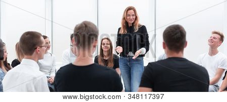 young woman conducts business training with a group of young people.