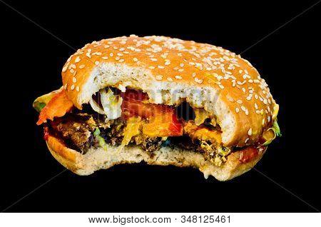 Half eaten hamburger on black