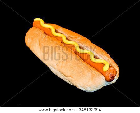 Hot dog and mustard on black