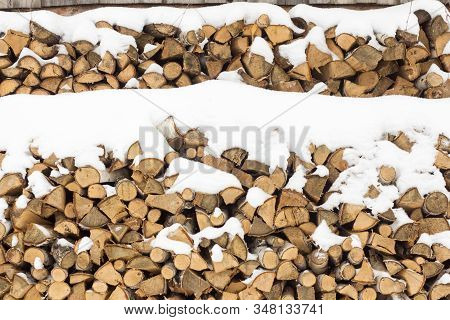 Stacked In A Woodpile For Heating The House In Winter.firewood Under The Snow.wood Fuel.