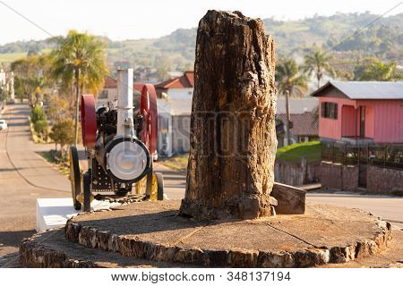 Fossilized Wood Trunk In The City Of Mata, Rs, Brazil. In The Background A Steam Engine. Mata Is A C