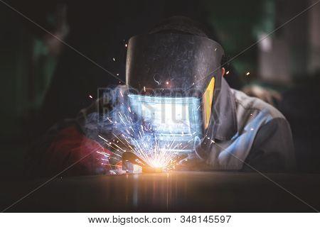 Welder Is Welding A Metal Frame Close Up.