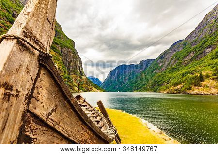Old Wooden Viking Boat On Fjord Shore. Mountains And Sognefjord. Tourism And Traveling Concept