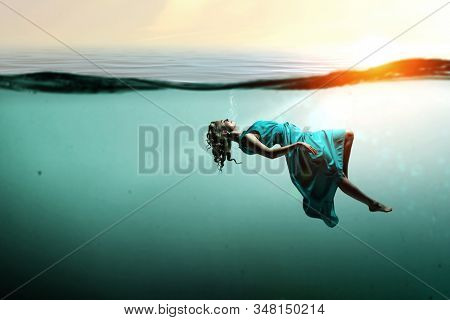 Woman dancer in clear blue water