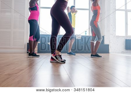 Side View Of Multicultural Dancers Exercising Zumba Choreography In Dance Studio