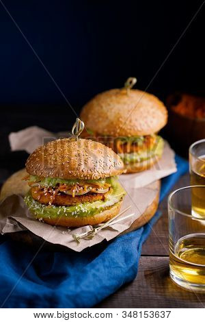 Vegan Sweet Potato Or Pumpkin Burgers With Avocado Guacamole Sauce And Carrot Slaw On Dark Blue Back