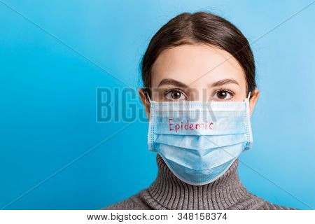 Portrait Of Young Woman Wearing Medical Mask With Epidemic Word At Blue Background. Protect Your Hea