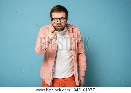 Disgruntled Caucasian man points index finger at someone and blames, looking into the camera with narrowed eyes. poster