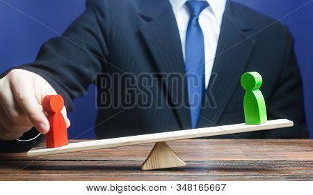 Man Opposes Green Figure To Red Opponent On Scales. Give An Advantage, Change Balance Of Power, Chan