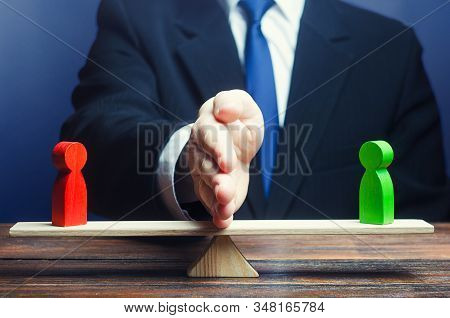 Man Divides Conflicting Sides Parties With A Hand On Scales. Avoidance Violence, Bullying. Protectio