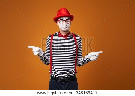 Seriouse mime in red hat and vest on orange background