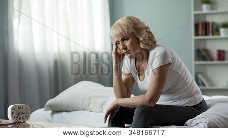 Adult Female Sitting Bed And Suffering From Migraine, Health Problem, Menopause