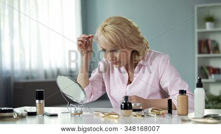 Female Blond Pensioner Looking At Hair In Mirror, Aging Process, Beauty Tips