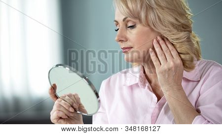 Beautiful Female In Her 50s Looking At Face Skin Mirror, Collagen Cream Effect