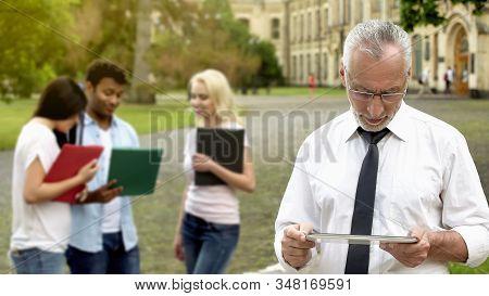 Senior Male Dean Scrolling Mobile App On Tablet, Technology In Education