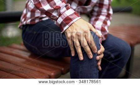 Man Sitting On Bench Feeling Sharp Knee Pain, Osteoarthritis, Injury, Healthcare