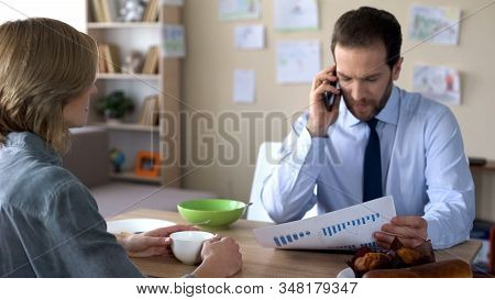 Busy Husband In Suit Discussing Company Statistics On Cellphone, Ignoring Wife